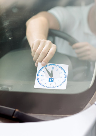 transportation and vehicle concept - man placing parking clock on car dashboard under windscreen photo