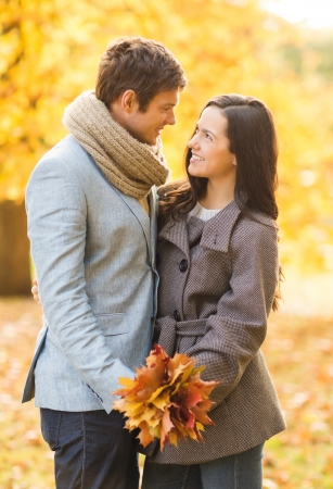 dating couples: holidays, love, travel, tourism, relationship and dating concept - romantic couple kissing in the autumn park