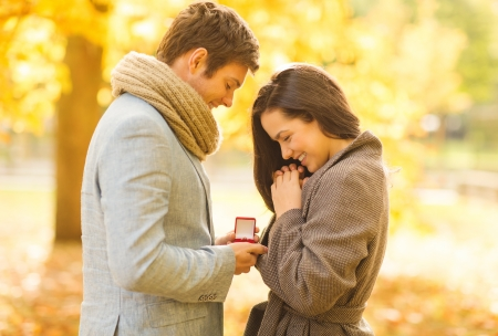 dating: holidays, love, couple, relationship and dating concept - romantic man proposing to a woman in the autumn park