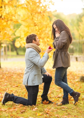 love couple: holidays, love, couple, relationship and dating concept - kneeled man proposing to a woman in the autumn park