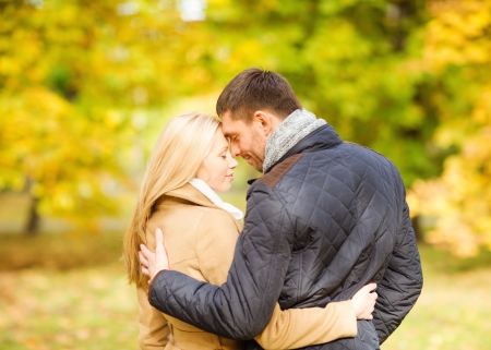 love kiss: holidays, love, travel, tourism, relationship and dating concept - romantic couple kissing in the autumn park