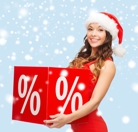 shopping, sale, gifts, christmas, x-mas concept - smiling woman in santa helper hat with percent sign photo