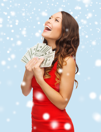 christmas, x-mas, sale, banking concept - smiling woman in red dress with us dollar money photo