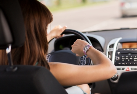 woman driving car: transportation and vehicle concept - woman driving a car and looking at watch