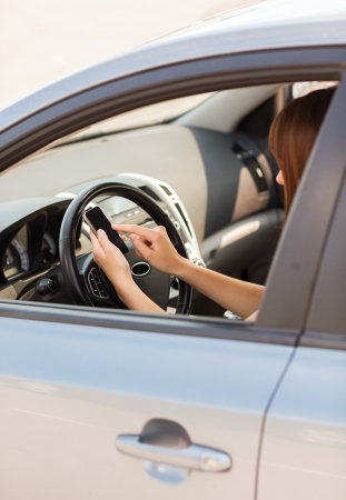 transportation and vehicle concept - woman using phone while driving the car photo