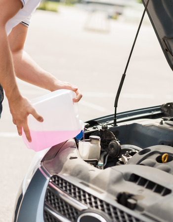 transportation and vehicle concept - man opening car bonnet and filling windscreen water tank with washing liquid photo