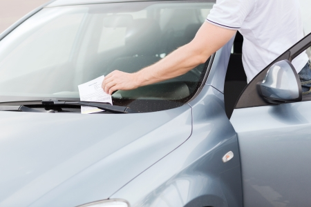 illegally: transportation and vehicle concept - parking ticket on car windscreen