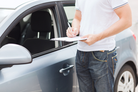 new car lot: transportation and ownership concept - man with car documents Stock Photo