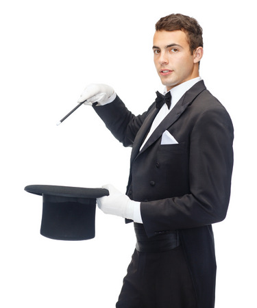 performance, circus, show concept - magician in top hat with magic wand showing trick photo
