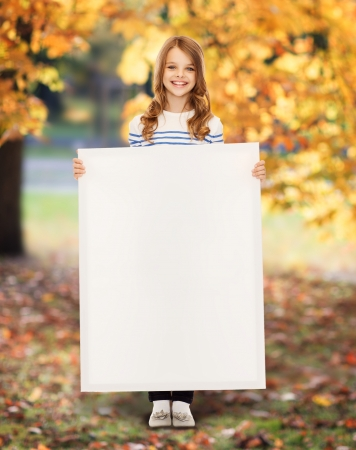 big smile: education and blank board concept - little girl with blank white board