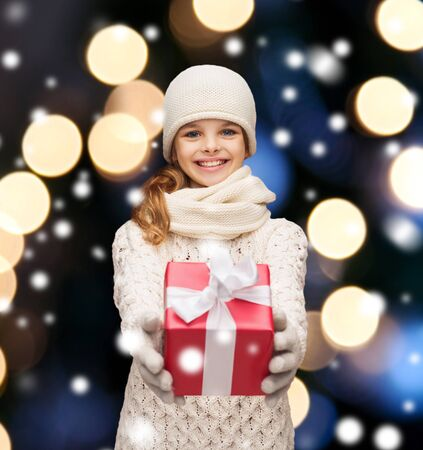 christmas, x-mas, winter, happiness concept - smiling girl in hat, muffler and gloves with gift box photo