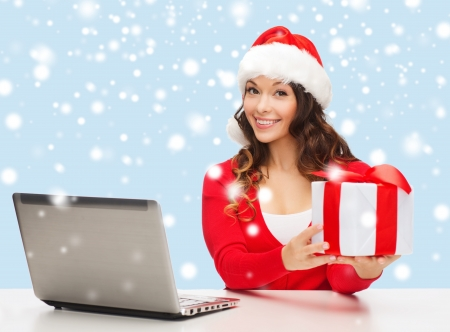 christmas, x-mas, online shopping concept - woman in santa helper hat with gift box and laptop computer photo