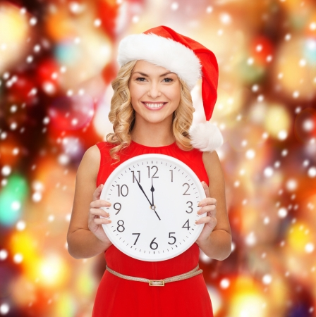 christmas, x-mas, winter, happiness concept - smiling woman in santa helper hat with clock showing 12 Stock Photo - 23318012