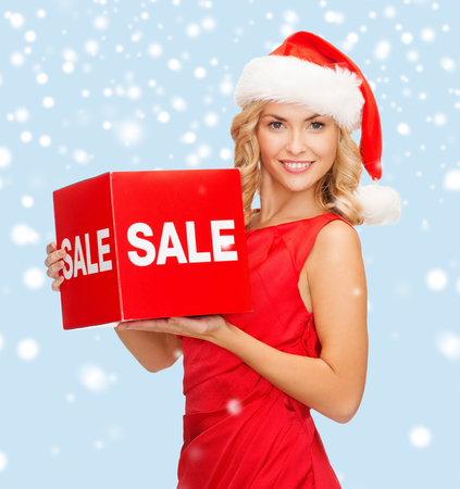 shopping, gifts, christmas, x-mas concept - smiling woman in santa helper hat with red sale sign photo