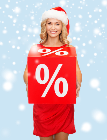 shopping, gifts, christmas, x-mas concept - smiling woman in santa helper hat with red percent sale sign photo