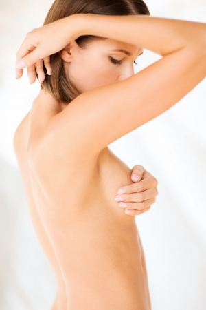 beautiful breasts: health, medicine, beauty concept - woman checking breast for signs of cancer Stock Photo
