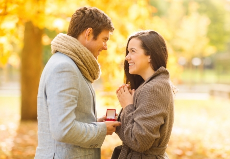 proposing: holidays, love, couple, relationship and dating concept - romantic man proposing to a woman in the autumn park