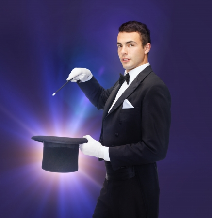 conjuring: performance, circus, show concept - magician in top hat with magic wand showing trick