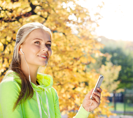 sport and lifestyle concept - woman doing sports and listening to music outdoors photo