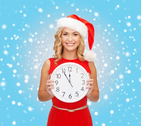 christmas, x-mas, winter, happiness concept - smiling woman in santa helper hat with clock showing 12 Stock Photo - 23451012