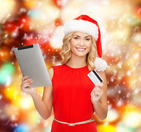 christmas, x-mas, online shopping concept - woman in santa helper hat with tablet pc computer and credit card photo