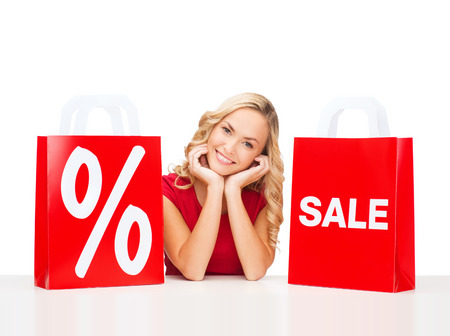 shopping, sale, gifts, christmas, x-mas concept - smiling woman in red dress with shopping bags and percent sign Stock Photo