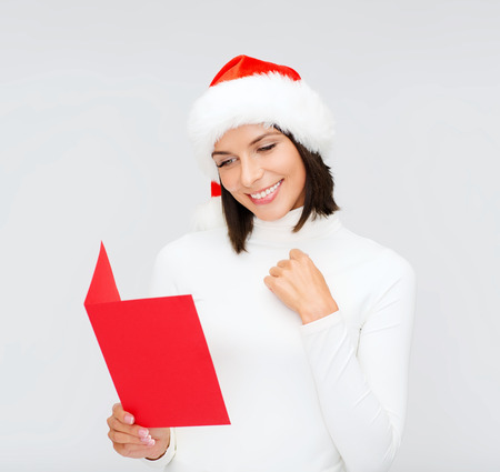 christmas, x-mas, people, advertisement, sale concept - happy woman in santa helper hat with blank red postcard photo