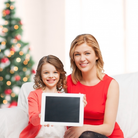 christmas, x-mas, winter, happiness, advertisement, modern technology concept - mother and daughter with tablet pc showing blank screen photo