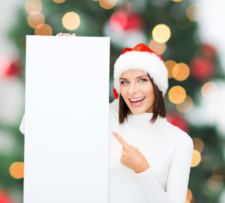 christmas, x-mas, people, advertisement, sale concept - happy woman in santa helper hat with blank white board photo