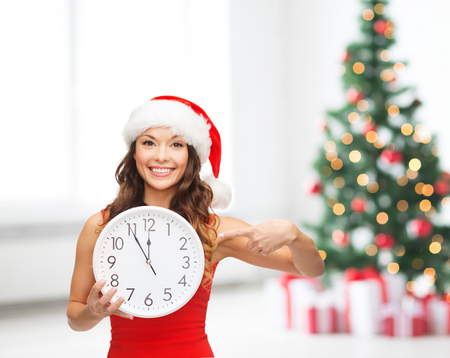 christmas, x-mas, winter, happiness concept - smiling woman in santa helper hat with clock showing 12 Stock Photo - 23451239