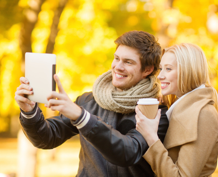 travel, tourism, modern technology, holidays and dating concept - couple taking photo picture with tablet pc camera in autumn park photo