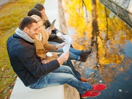 travel guide: holidays and tourism, navigation concept - group of friends or couples with tourist map and tablet pc computer in autumn park Stock Photo