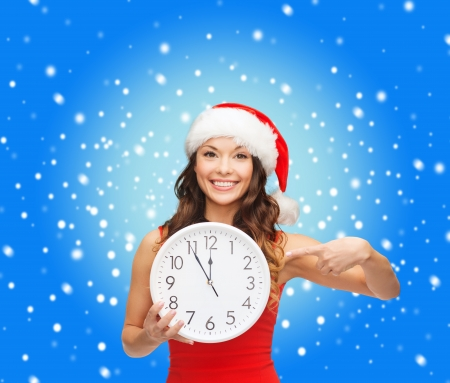 christmas, x-mas, winter, happiness concept - smiling woman in santa helper hat with clock showing 12 Stock Photo - 23451320