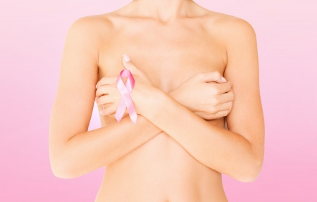 health, medicine, beauty concept - naked woman with breast cancer awareness ribbon Stock Photo