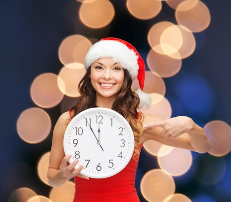 christmas, x-mas, winter, happiness concept - smiling woman in santa helper hat with clock showing 12 Stock Photo - 23451354