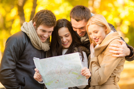 lost city: holidays and tourism concept - group of friends or couples with tourist map in autumn park
