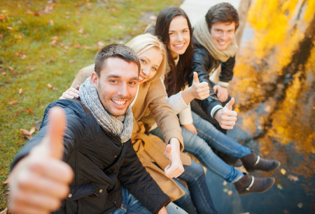 summer, holidays, vacation, happy people concept - group of friends or couples having fun and showing thumbs up in autumn park photo