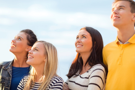 beautiful boys: summer, holidays, vacation, happy people concept - group of friends looking up on the beach