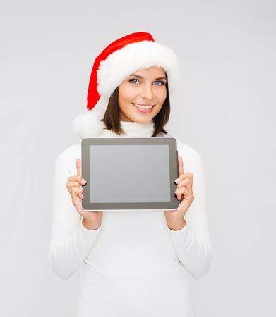 santa helper: christmas, x-mas, electronics, gadget concept - smiling woman in santa helper hat with blank screen tablet pc