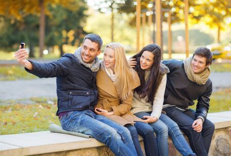 summer, holidays, vacation, travel, tourism concept - group of friends or couples having fun with smartphone photo camera in autumn park photo