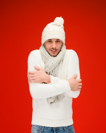 christmas, x-mas, winter, clothes concept - handsome man in warm sweater, hat and scarf photo