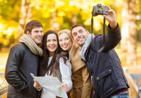 summer, holidays, vacation, travel, tourism, happy people concept - group of friends or couples having fun with photo camera in autumn park photo