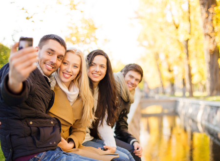 group picture: summer, holidays, vacation, travel and tourism concept - group of friends or couples having fun with smartphone photo camera in autumn park Stock Photo