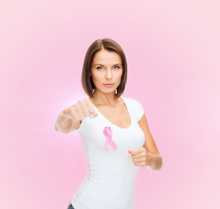 fighting cancer: healthcare and medicine concept - woman in blank t-shirt with pink breast cancer awareness ribbon