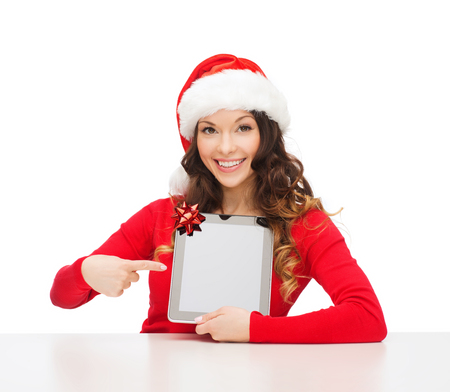 christmas, x-mas, electronics, gadget concept - smiling woman in santa helper hat with blank screen tablet pc photo