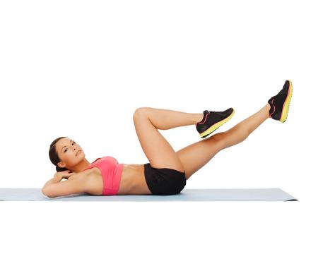 haciendo ejercicio: fitness, deporte, entrenamiento, gimnasio y concepto de estilo de vida - hermosa mujer deportiva haciendo ejercicios en el suelo Foto de archivo