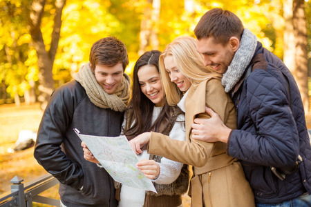 visitors: holidays and tourism concept - group of friends or couples with tourist map in autumn park