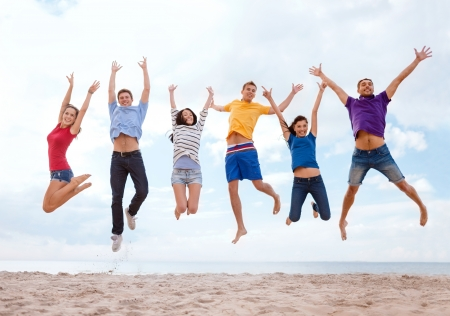 summer, holidays, vacation, happy people concept - group of friends jumping on the beach Фото со стока