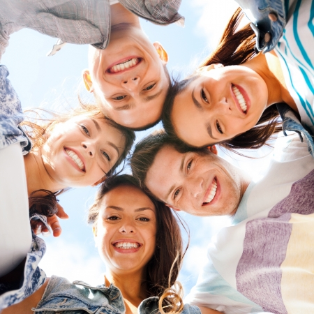 urban culture: summer holidays and teenage concept - group of teenagers looking down Stock Photo
