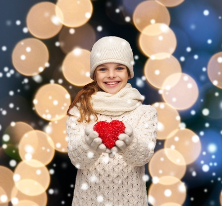 seasonal, people, happiness , health, charity, love concept - smiling teenage girl in winter clothes with small red heart photo